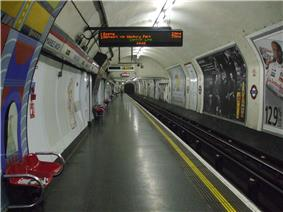 The interior of a building with rounded ceiling and walls, red benches along the left wall, advertisements along the right wall, and a yellow line on the floor