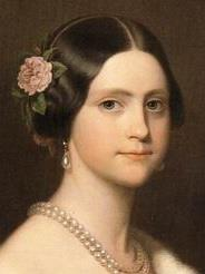 Painted head and shoulders portrait of a young woman wearing an ermine stole thrown over one shoulder, a double strand of large pearls around her neck, pearl drop earrings, and a pink camellia arranged in the hair over her right ear