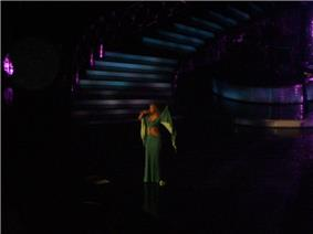 A woman is performing a song on stage. She is wearing a greenish dress.