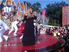 A woman wearing a long black gown. She has long golden hair and is holding a sparkling microphone. She is standing on a large red stage, surrounded by dancers in white attire. Additional background scenery include the audience and three background singers wearing white ensembles and standing on a large platform.