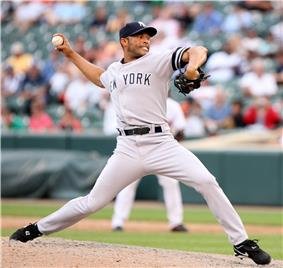 A right-handed Hispanic baseball pitcher, wearing a grey uniform with the lettering