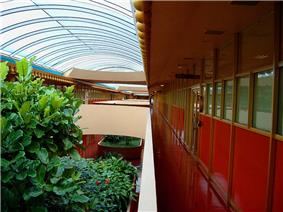 Interior photograph of the Marin County Civic Center. The skylit, two-story atrium has plantings, few sharp corners, and lots of reds and pinks.