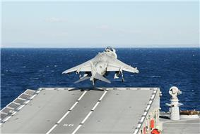 Back view of an aircraft taking off from a ramp aboard a ship. The ship is at sea.