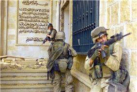 photograph of three Marines entering a partially destroyed stone palace with a mural of Arabic script