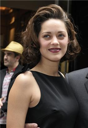 Headshot of a brown-haired French female wearing a black dress.