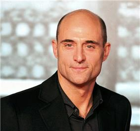 A head-and-shoulders view of a bald middle-aged Strong, wearing a dark shirt and black jacket.