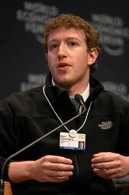 Waist high portrait of man in his twenties, looking into the camera and gesturing with both hands, wearing a black pullover shirt that says