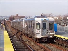 A silver subway train leaving a station.