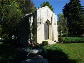 White stone mausoleum with iron doors and