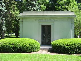 A large stone tomb with a metal gate in the center of the tomb, and with carved columns at the corners meeting a crest which circles the top of the building. Two large evergreen bushes obscure the lower portion of the tomb which sits in a grassy meadow.