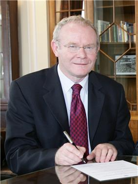 smiling man with glasses, holding a pen
