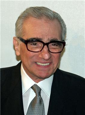 Headshot of a Caucasian male with thick rimmed glasses. He is wearing a black suit over a white shirt with a green tie.
