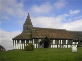 A timber-framed church with a small tower and spirelet