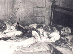 Kelly's eviscerated body lying on a bed. Her face is mutilated.