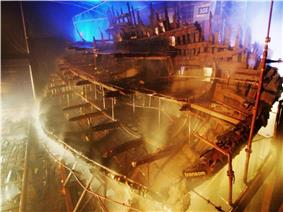 A diagonal section of a wooden ship seen from the stern inside a moodily lit building while it is being sprayed with water from a sprinkler system
