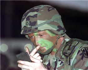 photo of a soldier putting on camouflage face paint