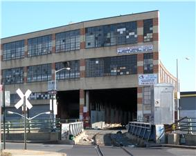 The Bushwick Branch, a single-track railroad, crosses Flushing Avenue on a bridge and then goes into the Maspeth Industrial Center, an industrial building