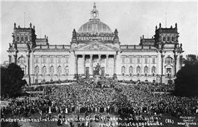 Thousands of people gather in front of a building.