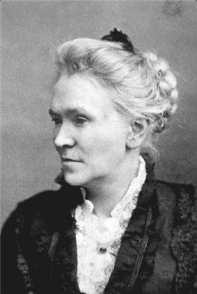 Chest high portrait of a middle aged woman wearing a dark dress and white shirt, hair up in a bun
