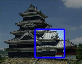 A two-storied tower connected on one side to a five-storied castle tower and on the other to a lower one-storied structure. All three structures have black wooden walls and are located on a platform of unhewn stones.