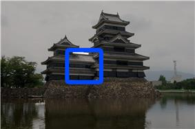 A 2-storied structure connecting a 3-storied castle tower with a 5-stoired tower. All three structures have black wooden walls and are located on a platform of unhewn stones above a water filled moat.