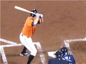 A man wearing an orange baseball uniform holding a baseball bat over his right shoulder