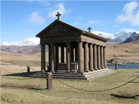 A stone building, with open sides lined by columns sits in a grassy meadow. A low fence made of small posts and a single chain surrounds it. Tall snow-clad mountains in the background lie under a blue sky.