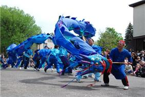 people watching about seven street dancers with a large blue dragon puppet