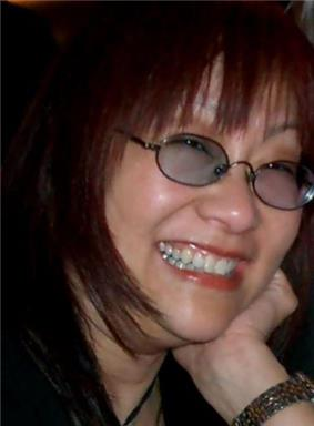 Profile picture of a bespectacled Asian woman in her early fifties. She has long red hair, and shows a toothy smile.