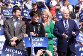 Todd Palin, Sarah Palin (behind a podium), Cindy McCain, John McCain together on an outdoor stage during daytime, crowd holding blue-and-white