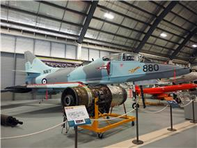 Colour photograph of a military fighter jet aircraft painted in blue and grey camouflage in a museum other aircraft and engines are visible.
