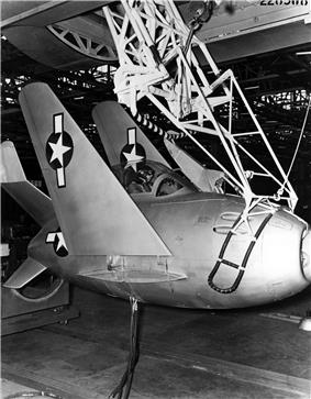 Black-and-white photograph of small egg-shaped fighter aircraft hoisted by a lifting mechanism underneath a large bomber.