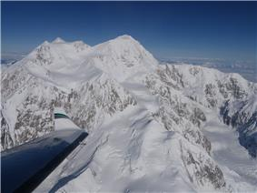 An aerial view of Denali; an airplane wing is visible in the lower-left corner