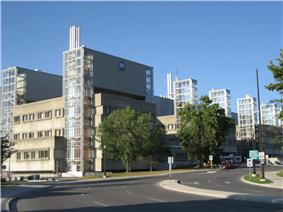 A road curves from the bottom to the right, where it is lined with several deciduous trees. Adjacent to it throughout the image is a broad three-storey beige building with newer rectangular five-storey glass extensions at its periphery. There are six regularly-spaced glass additions visible.