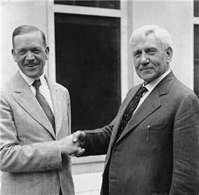 Two smiling middle-aged men in business suits shake hands in front of a window. They are standing but are visible only from the waist up.