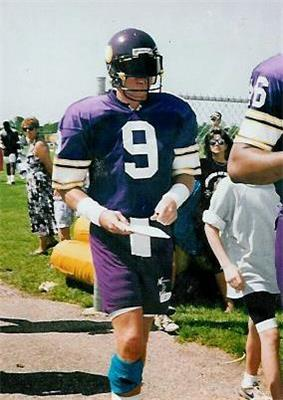 A white man wearing a purple jersey with white trim and a large numeral