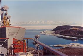 In left foreground are the upper works of a modern ship. To the right, on a low headland fringed with sea ice, isa square hut with a pitched roof. In te distance is a range of icy mountains