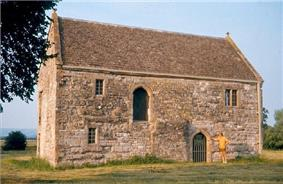 Yellow stone building with tiled roof and arched doorway.