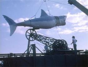 A large model shark is hoisted by a crane as two men watch it.