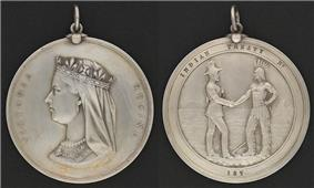 Photograph showing the two sides of a round silver medal, showing the profile of Queen Victoria on one side and the inscription