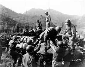 A group of medics lift several wounded soldiers onto a tracked vehicle