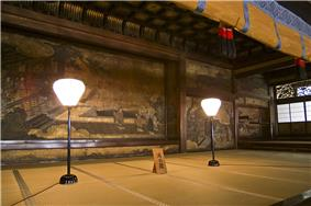 Tatami matted room with a large scale wall painting of a court scene.