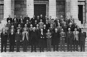 Around thirty men standing on steps.