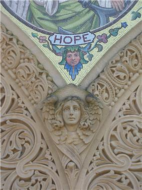 A carving of the head and wings of an angel: above the angel is the bottom of a mosaic with the label