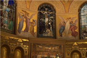 A stained glass window shows the crucifixion. On either side mosaics show angels holding symbols of the Passion and Glory of Christ. Beneath is a mosaic depicting Christ and His apostles celebrating the Passover.