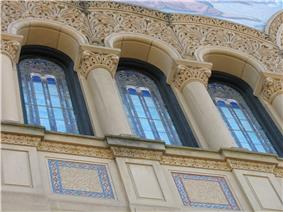The upper windows of the facade are surrounded by rich carvings.