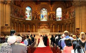 Looking down the center aisle at a bride and groom standing before a minister in front of the altar: a red carpet covers the floor of the aisle, and the church is full of on-lookers.