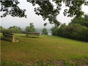 A bench and a picnic table on a grassy slope with a lake visible through trees in the distance