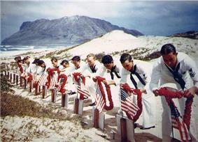 Photograph of a 1942 memorial service at Kaneohe Naval Air Station, showing sailors placing leis on graves of men killed during the Pearl Harbor Attack.