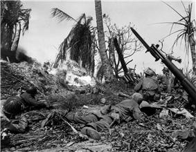 A group of soldiers crawling through a burning jungle, with a hidden bunker in front of them